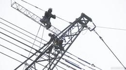 Monteure ziehen Stromleitungen auf 70 Meter hohen Strommasten auf